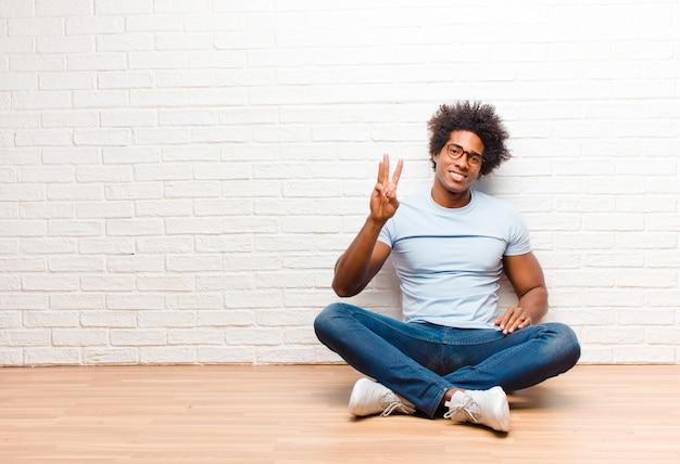 Młody murzyn uśmiecha się i wygląda przyjaźnie, pokazuje numer trzy lub trzeci z ręką do przodu, odliczając czas siedzenia na podłodze w domu