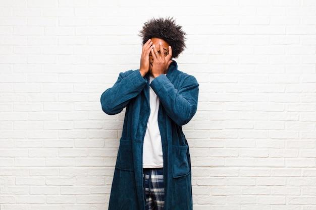 Młody murzyn w piżamie z suknią czuje się przestraszony lub zawstydzony, zerkając lub szpiegując oczy na wpół zasłonięte rękami przed ścianą