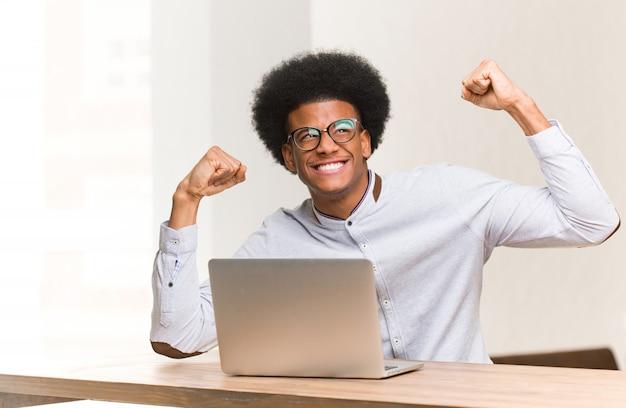 Młody murzyn za pomocą swojego laptopa, który się nie poddaje