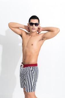 Młody muskularny facet w pasiastych spodenkach plażowych do opalania nosić okulary przeciwsłoneczne izolowane na białej powierzchni