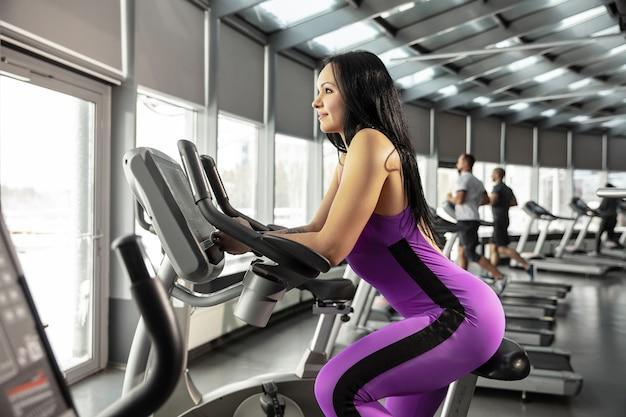 Młody muskularny kaukaski kobieta ćwiczy w siłowni z cardio. lekkoatletyczna modelka robi ćwiczenia prędkości, trenuje jej dolną, górną część ciała.