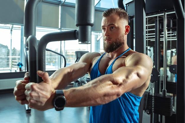 Młody muskularny kaukaski sportowiec trenuje na siłowni, robi ćwiczenia siłowe, ćwiczy, pracuje nad górną częścią ciała, ciągnie na ciężarki i sztangę. fitness, wellness, koncepcja zdrowego stylu życia, praca.