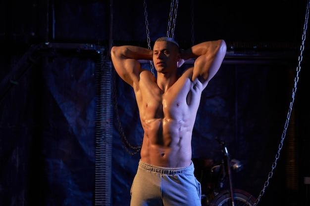 Młody, muskularny mężczyzna bez koszuli stojący wśród metalowych łańcuchów, patrzący poważnie w kamerę, kopiujący przestrzeń tyłem do aparatu