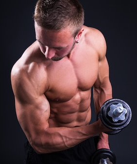 Młody muskularny mężczyzna robi ćwiczenia z hantlami na szarym tle
