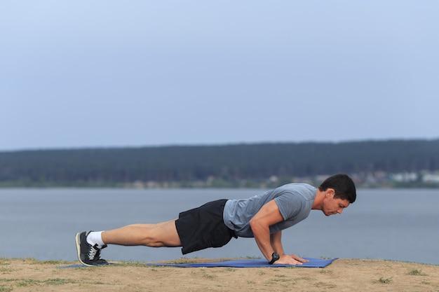Młody muskularny mężczyzna robi pompki na zewnątrz