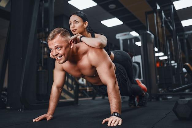 Młody muskularny mężczyzna robi pushup ćwiczenia i trzymając dziewczynę wspólne lekcje grupowe szkolenia teambuilding romans