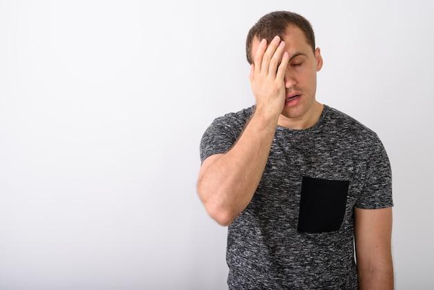 Młody muskularny mężczyzna szuka zmęczonego, zasłaniając twarz