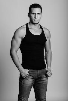 Młody muskularny perski mężczyzna stojący przy szarej ścianie
