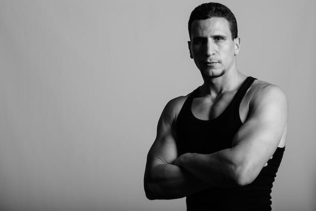 Młody, muskularny perski mężczyzna ubrany bez rękawów z rękami skrzyżowanymi na szarej ścianie