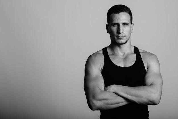 Młody muskularny perski mężczyzna z rękami skrzyżowanymi na szarej ścianie