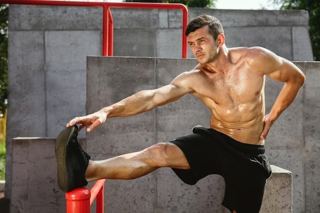 Młody muskularny przystojny kaukaski mężczyzna robi ćwiczenia rozciągające na placu zabaw w słoneczny letni dzień.