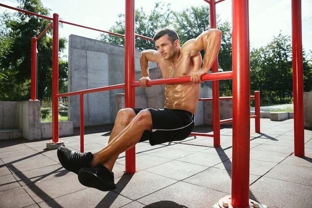 Młody muskularny przystojny kaukaski mężczyzna robi podciągnięcia na poziomym pasku