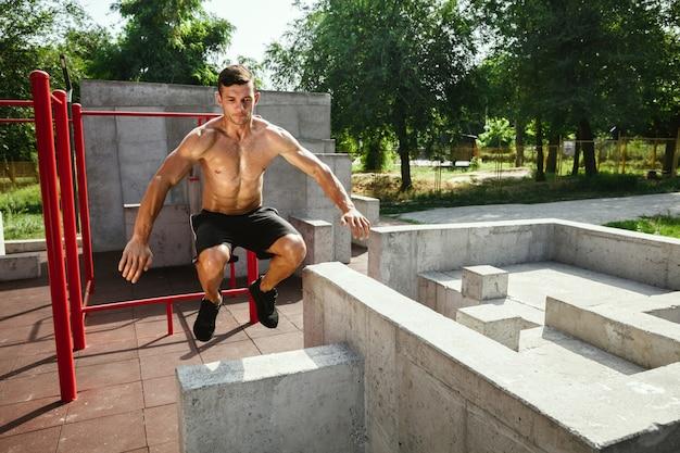 Młody muskularny przystojny kaukaski mężczyzna skoki powyżej poziomego paska na placu zabaw w słoneczny letni dzień. trening górnej części ciała na zewnątrz. pojęcie sportu, treningu, zdrowego stylu życia, dobrego samopoczucia.
