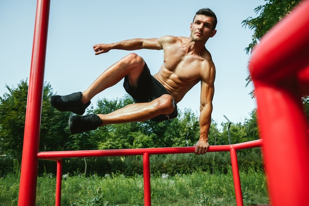 Młody muskularny przystojny kaukaski mężczyzna skoki powyżej poziomego paska na placu zabaw w słoneczny letni dzień