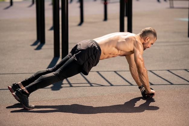 Młody muskularny sportowiec bez koszuli w czarnych spodenkach, leginsach i trampkach pochylający się nad boiskiem sportowym podczas ćwiczeń z rolowanym trymerem