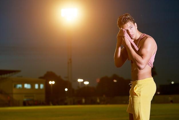 Młody muskularny sportowiec ociera pot z twarzy koszulą na stadionie