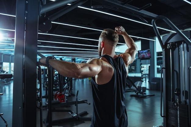 Młody muskularny sportowiec rasy kaukaskiej trenujący na siłowni, wykonujący ćwiczenia siłowe