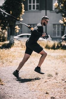 Młody muskularny sportowiec trenujący z opaskami trx w parku