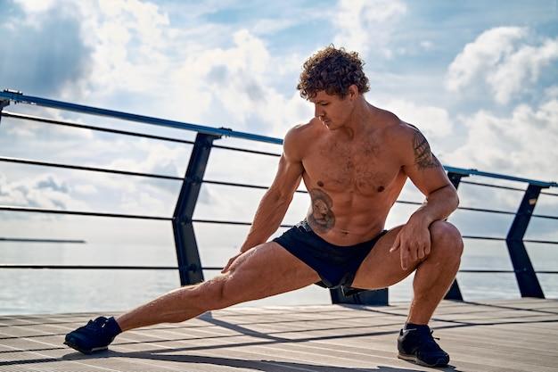 Młody muskularny wytatuowany mężczyzna robi ćwiczenia rozciągające wcześnie rano na molo nad morzem