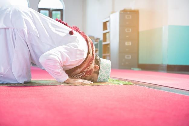 Młody muzułmański arabski mężczyzna siedzi na kolanie i dotyka głowy podłogi w meczecie