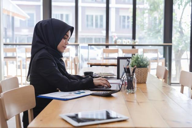 Młody muzułmański bizneswoman pracuje przy biurem
