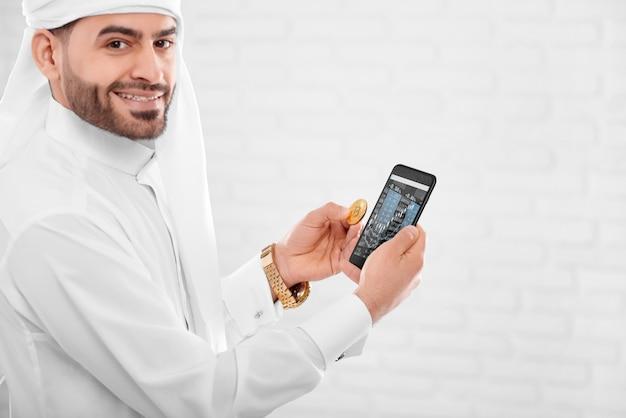 Młody muzułmański kupiec trzyma złote bitcoiny i telefon komórkowy