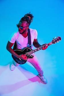 Młody muzyk afro-amerykański gra na gitarze jak gwiazda rocka na niebieskiej ścianie w świetle neonów.
