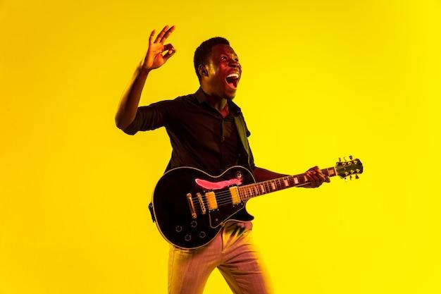 Młody muzyk afro-amerykański gra na gitarze jak gwiazda rocka na żółtym tle w świetle neonów. koncepcja muzyki, hobby, festiwalu, pleneru. radosny facet improwizujący, śpiewający piosenkę.