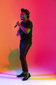 Młody muzyk afro-amerykański śpiewa na gradientowym tle pomarańczowo-fioletowym studio w świetle neonowym. pojęcie muzyki, hobby, festiwalu. radosny gospodarz imprezy, stań wyżej. kolorowy portret artysty.