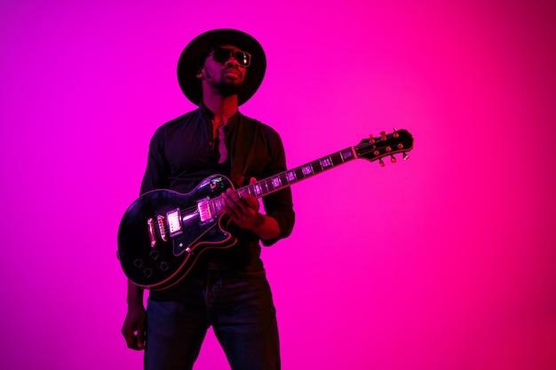 Młody muzyk afroamerykański grający na gitarze jak gwiazda rocka na gradientowym fioletowo-różowym tle w świetle neonu.