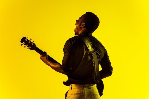 Młody muzyk afroamerykański grający na gitarze jak gwiazda rocka na żółtym tle w świetle neonu.
