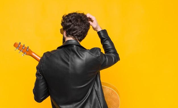 Młody muzyk czujący się nieświadomy i zdezorientowany, zastanawiający się nad rozwiązaniem, z ręką na biodrze i innymi na głowie, widok z tyłu z gitarą, rock and rolla