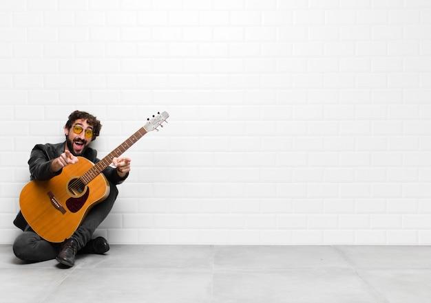 Młody muzyk czuje się szczęśliwy i pewny siebie, wskazując aparat obiema rękami i śmiejąc się, wybierając cię z gitarą