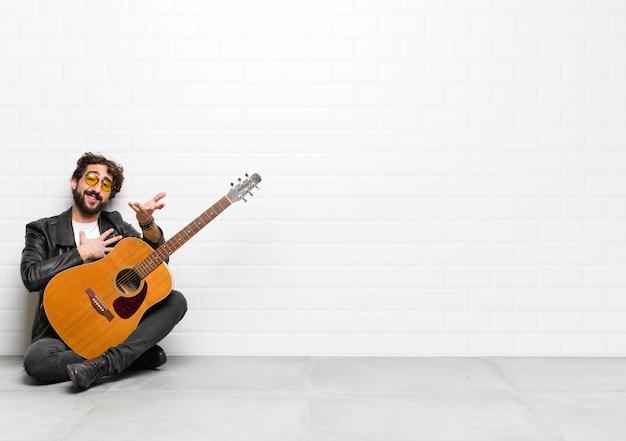 Młody muzyk czuje się szczęśliwy i zakochany, uśmiechając się jedną ręką obok serca, a drugą wyciągnął z przodu z koncepcją gitary, rock and rolla
