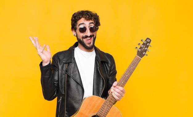 Młody muzyk czuje się szczęśliwy, zaskoczony i wesoły, uśmiecha się z pozytywnym nastawieniem, realizując rozwiązanie lub pomysł z koncepcją gitary, rock and rolla