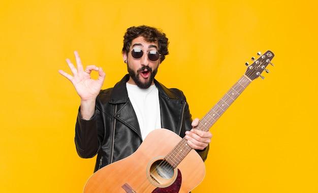 Młody muzyk czuje się szczęśliwy, zrelaksowany i zadowolony, pokazując zatwierdzenie z dobrym gestem, uśmiechając się z koncepcją gitary, rock and roll