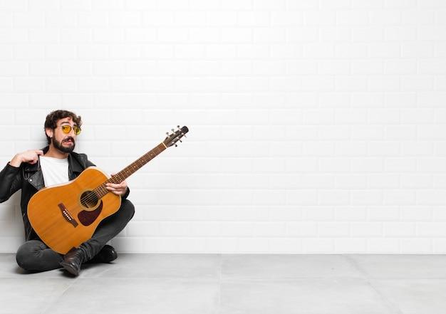Młody muzyk czuje się zestresowany, niespokojny, zmęczony i sfrustrowany, ciągnie szyję koszuli, wygląda na sfrustrowanego problemem z koncepcją gitary, rock and rolla