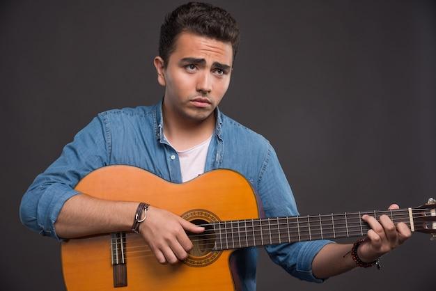 Młody muzyk gra na gitarze na czarnym tle