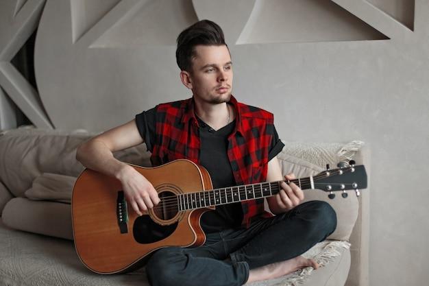 Młody muzyk gra na gitarze