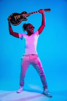 Młody muzyk grający na gitarze jak gwiazda rocka na niebieskim tle w świetle neonu.