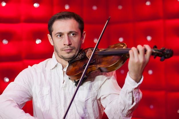 Młody muzyk grający na skrzypcach w restauracji na czerwonej ścianie.