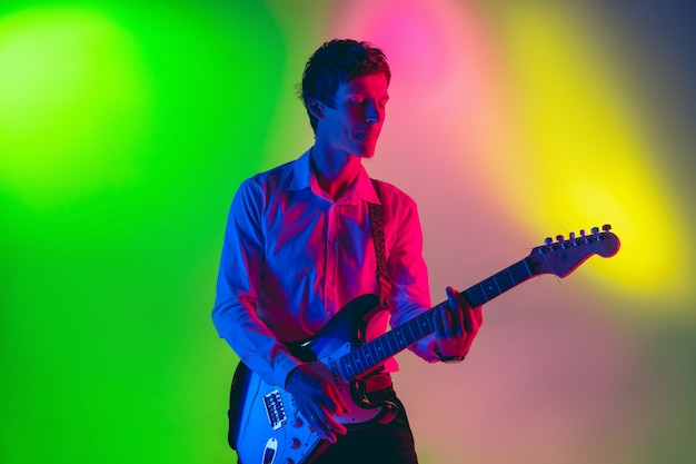 Młody muzyk kaukaski, gitarzysta grający na przestrzeni gradientu w świetle neonu. pojęcie muzyki, hobby, festiwalu