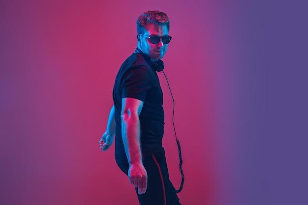 Młody muzyk kaukaski w słuchawkach śpiewa na gradientowej różowo-fioletowej ścianie w świetle neonowym. koncepcja muzyki, hobby, festiwalu. radosny gospodarz imprezy, dj, stań na górze. kolorowy portret artysty.