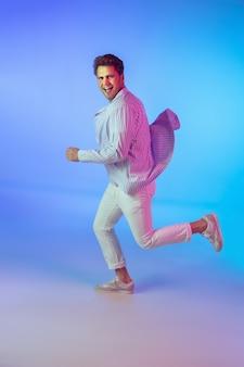 Młody muzyk kaukaski w swobodnym tańcu na niebieskim tle gradientu w świetle neonowym. pojęcie muzyki, hobby, festiwalu. radosny gospodarz imprezy, dj, górna trybuna, tancerka. kolorowy portret artysty.
