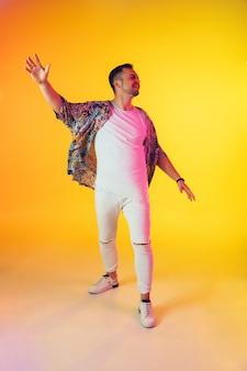 Młody muzyk kaukaski w swobodnym tańcu na żółtym tle gradientu w świetle neonowym. pojęcie muzyki, hobby, festiwalu. radosny gospodarz imprezy, dj, górna trybuna, tancerka. kolorowy portret artysty.