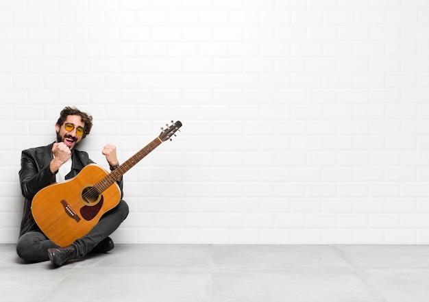 Młody muzyk krzyczy triumfalnie, śmiejąc się, czując się szczęśliwy i podekscytowany, świętując sukces z koncepcją gitary, rock and rolla