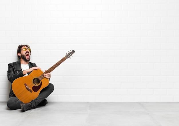 Młody muzyk krzyczy wściekle, krzyczy agresywnie, wygląda na zestresowanego i wściekłego na gitarę, rock and rolla