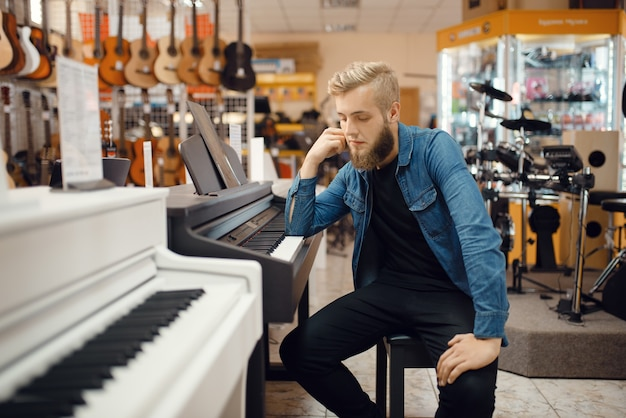 Młody muzyk mężczyzna pozuje przy fortepianie w sklepie muzycznym. asortyment w sklepie z instrumentami muzycznymi, zakup sprzętu klawiszowca, pianista na rynku