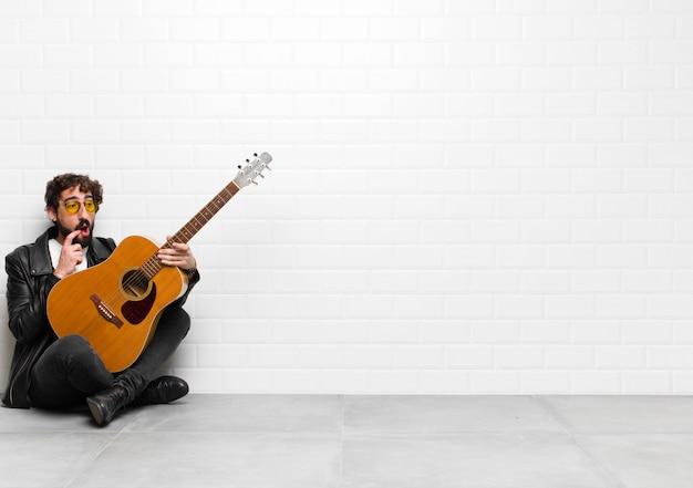 Młody muzyk o zdziwionym, nerwowym, zmartwionym lub przestraszonym spojrzeniu, patrzy w bok w kierunku kopii przestrzeni z koncepcją gitary, rock and rolla
