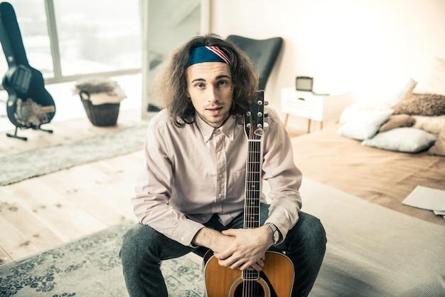 Młody muzyk odpoczywa. przyjemny profesjonalny gitarzysta w lekkiej koszuli i bandanie, trzymając swój osobisty instrument